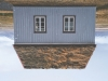 A photograph of an upside-down house with a cultivated sod roof