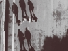 Three youths photographed from above, their shadows producing three upright figures trailing behind them