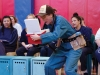 Spectators watch as an actor in costume peers inside of a mini-cooler