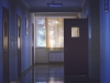 A hallway in a hospital with an door open just before a window lit by the sun