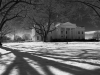 A black and white photo of the White House, seen with long tree shadows lain ominously across the snowy ground