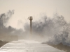 An observation tower rises out of the swirling froth atop a sea wall