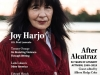 Joy Harjo, clad in a dark red coat against a snowy backdrop, looks directly at the viewer
