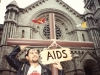 "A man in a leather jacket carries a cross with a sign hanging around it that reads, ""AIDS,"" while standing in front of a church"