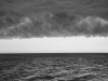 A black and white photo of the sea, dark clouds looming overhead, with the horizon forming the only light between them