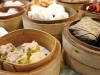 Small dishes of food in bamboo bowls on a dim sum cart