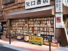 A Japanese salaryman pauses at a bookstall on the corner of two intersecting streets