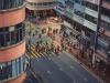 A shot from above as a throng of people cross a city street