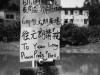 """A hand-lettered sign in Chinese with English words that read """"To Yuen Long / Please Press Bell"""""""