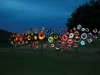 Many round objects, painted like bird's eye are mounted to poles and illuminated at night