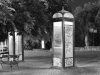 A black and white photo of phone booths, tagged with graffiti and lit up from the inside