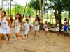 Children, dressed in white, dance in a line while holding hands