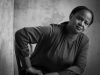A black and white photo of Edwidge Danticat, seated but leaning forward slightly, with her hand on her leg