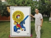 Youssouf Amine Elalamy standing next to a human sized playing card. He points to the tip of a sword.