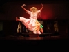 A dancer, clothed in a full length housedress, her face obscured, leaps across the stage