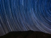 A time elapsed photo of the sky at night, the stars creating arcs of light across the sky