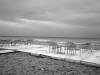 A black and white photos of empty tables and chairs on a patio overlooking a restless sea