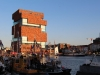 A blocky, multi-story building rises out of a river in Antwerp