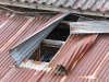 A photograph of a corrugated tin roof, partially peeled back