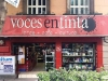 A photograph of a red bookstore front from the street. The sign above reads: Voces en Tinta with a subheading that reads: Libros + Cafe + Cultura