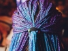 A photograph of the back of a person's head. They have tight braids, the outer layer of which dyed blue and purple