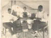 Two African American men seated at a table in a tent. Law books are stacked on the table. A woman stands at the entrance to the tent in the background.