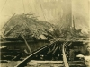 A sepia-toned photograph of a set of railroad tracks, which have been destroyed, with a city in rubble in the background