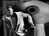 A surreal photograph depicting an African-American man dressed in a suit and carrying a briefcase is running as a giant eye scrutinizes him in the background