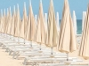 A row of umbrellas over reclining benches stretching into the distance by edge of the ocean against a light blue sky