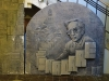 A stone sculpture of Ismail Kadare surrounded by books