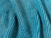 A close up photograph of the texture of a teal cloth
