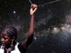 A girl holds a taut wire above her head with deep space in the background