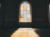 A photograph of a stained glass window from inside a darkened room with the color and light through the window projecting on to the floor