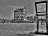 A black and white photograph of an empty town's square, with a chair that faces away from the viewer dominating the right side in the foreground