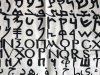 A photograph of the alphabet, each line in a different script, painted on a loose, white cloth