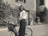 A black and white photo of Sylvia Plath with her bicycle smiling at the camera