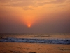 A red sun rises over the surf at dawn