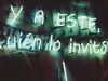 "A neon sign glows in the shadows of night. The text reads 'Y A Este wién lo invito"""