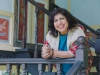 Dipika Mukherjee leans over a railing, smiling, as she looks at the camera