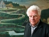 Author Tankred Dorst standing in front of a painting of a road winding up a mountain