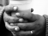 A black and white photograph of a pair of hands grasping a plastic coffee cup