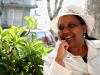 Ribka Sibhatu sits in a white suit and hat in front of a bush