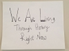 A hand-written sign. Text reads: We are living through history right now.