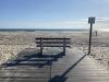A photograph of an empty bench facing the ocean