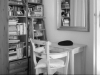 A black and white photo of a chair and desk sitting next to a bookshelf