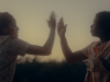 Two women standing face to face at sunset, arms raised in front of them until their hands almost touch