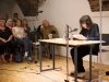 Friederike Mayröcker sits at a table reading with a small group sitting to the side