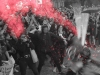 A black and white photo of protesters, mostly female, throwing glitter bombs, which are highlighted in red