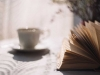 A teacup sits, out of focus, next to a book on a table.