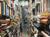 Looking down a narrow path with walls crammed with books looming in from both sides